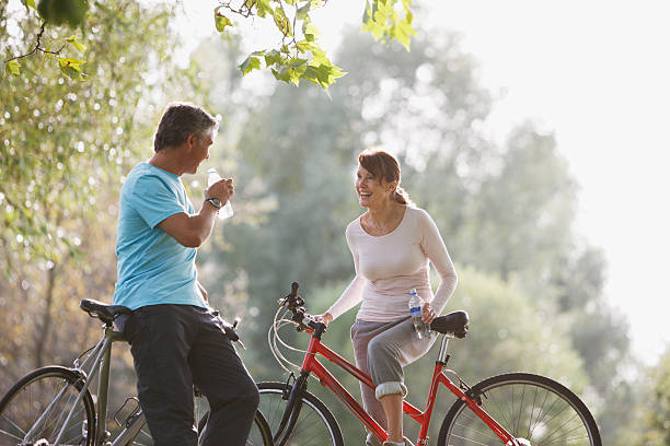 Couple with bicycles drinking water stock photo