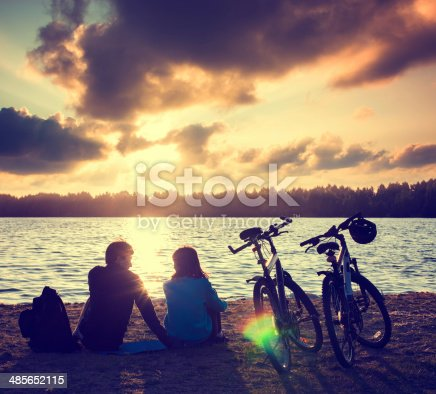969439086istockphoto Couple with Bicycles Relaxing at Sunset 485652115