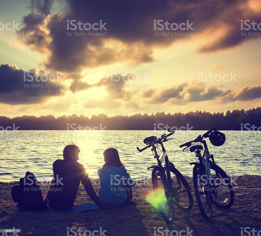 Couple with Bicycles Relaxing at Sunset stock photo