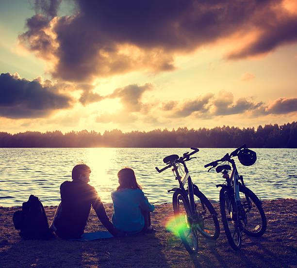 Paar mit Fahrräder Entspannen bei Sonnenuntergang – Foto