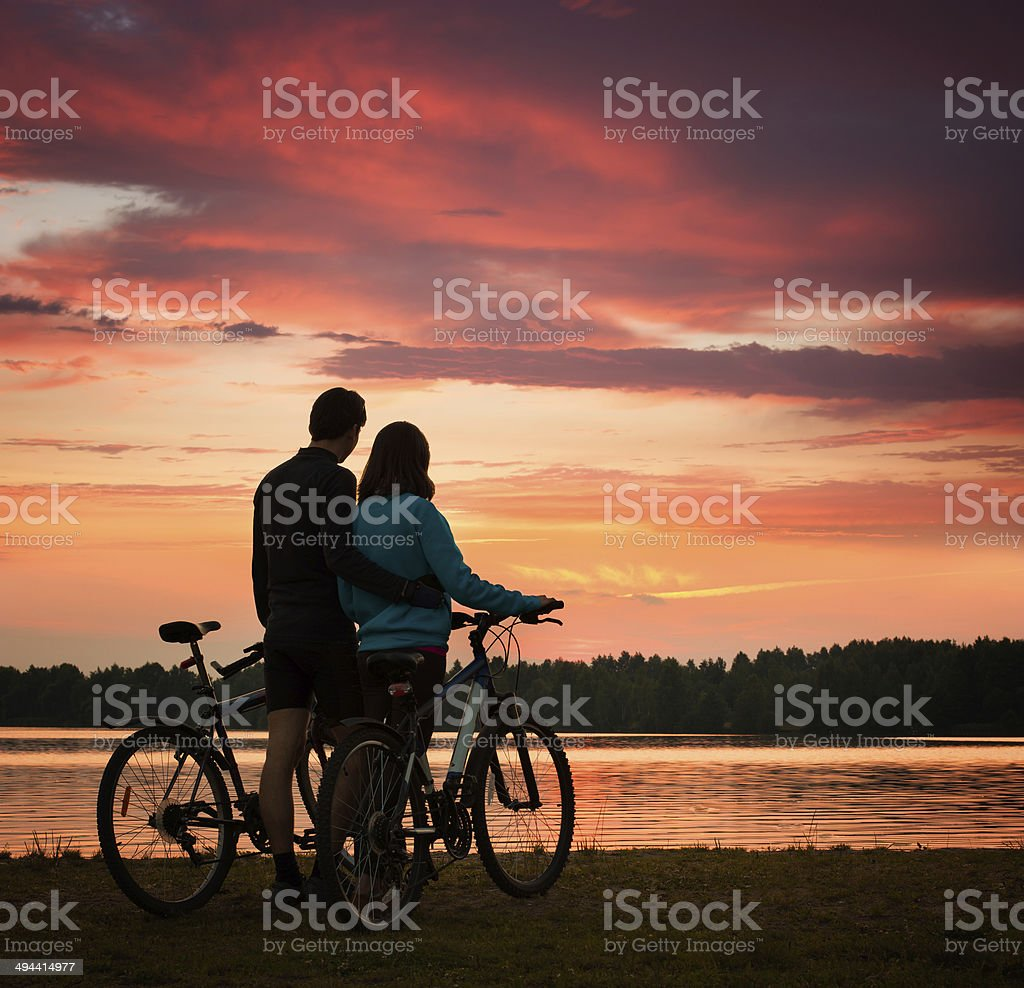 Couple with Bicycles Watching Sunset at River stock photo