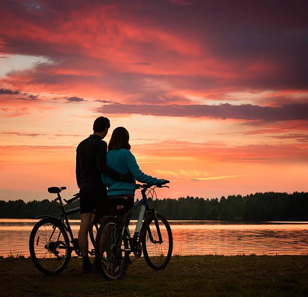 Paar mit Fahrräder Sonnenuntergang am Fluss – Foto
