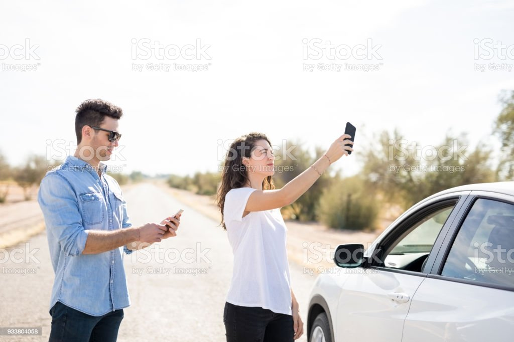 Couple with broken car searching for phone coverage stock photo