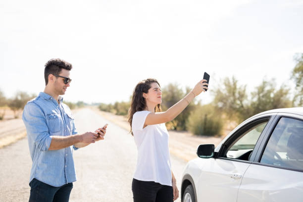 couple with broken car searching for phone coverage - stranded stock pictures, royalty-free photos & images