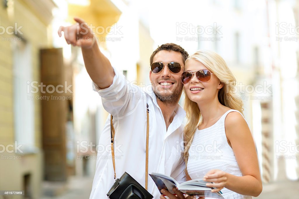 couple with camera and travellers guide in city stock photo