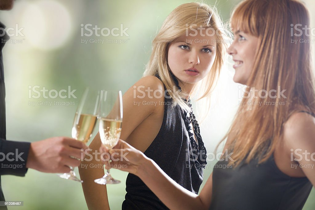 Couple with champagne glasses and woman looking at them, outdoors stock photo