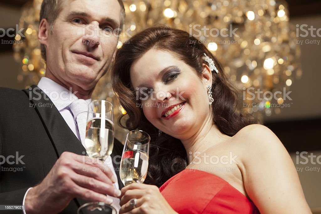 Couple with Champagne under chandelier stock photo