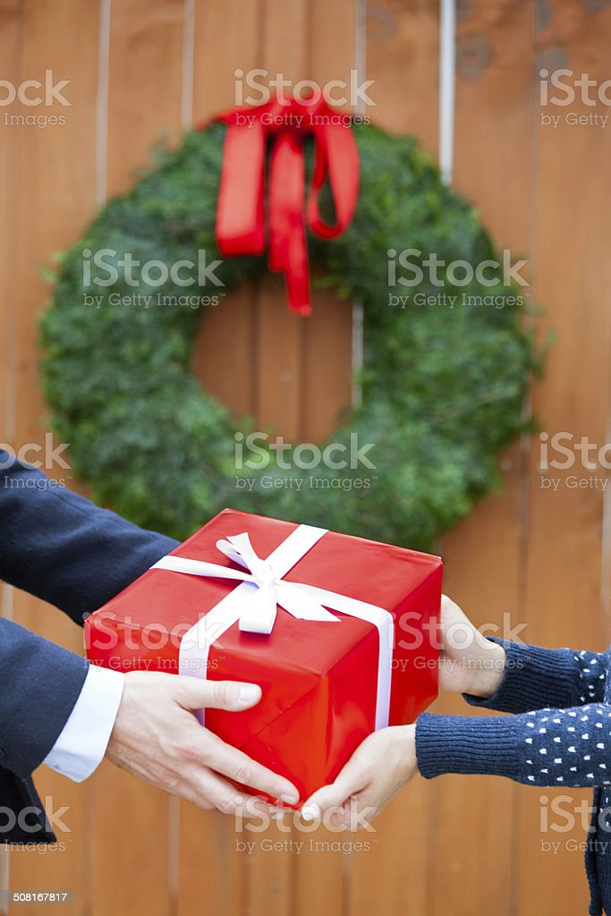 Couple with christmas gift Close up of female and male hands holding christmas girf against door decorated with christmas wreath. Adult Stock Photo