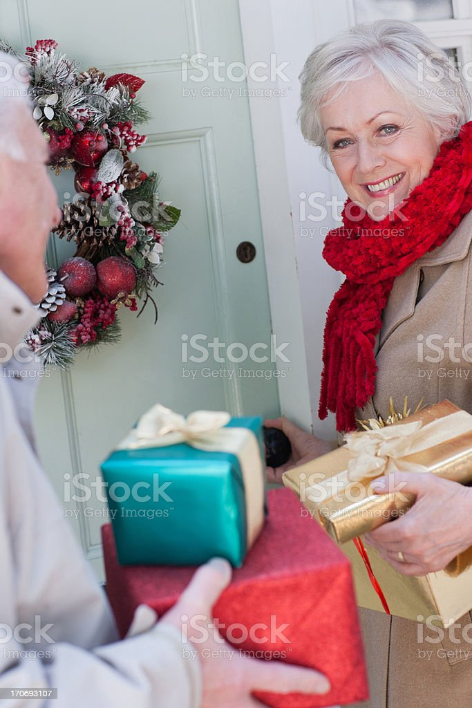 Couple with Christmas gifts standing at door royalty-free stock photo