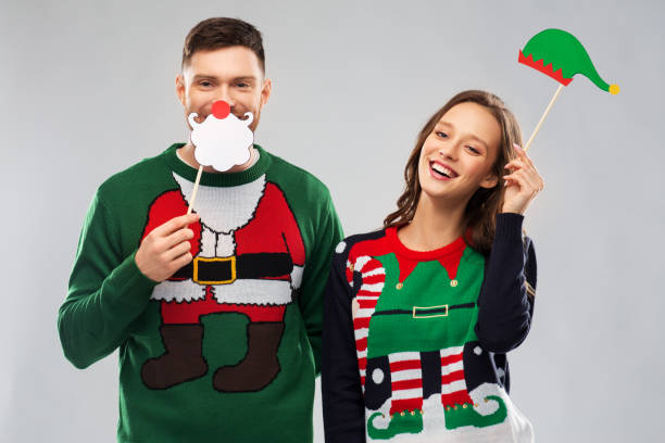 couple with christmas party props in ugly sweaters stock photo