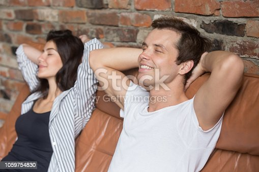 938682762istockphoto Couple with closed eyes sitting relaxing on couch at home 1059754830