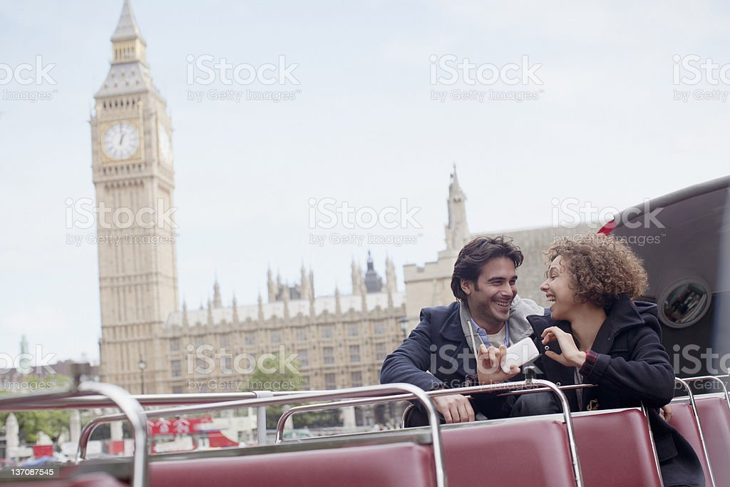 Couple with digital camera riding double decker bus near Big Ben clocktower in London stock photo