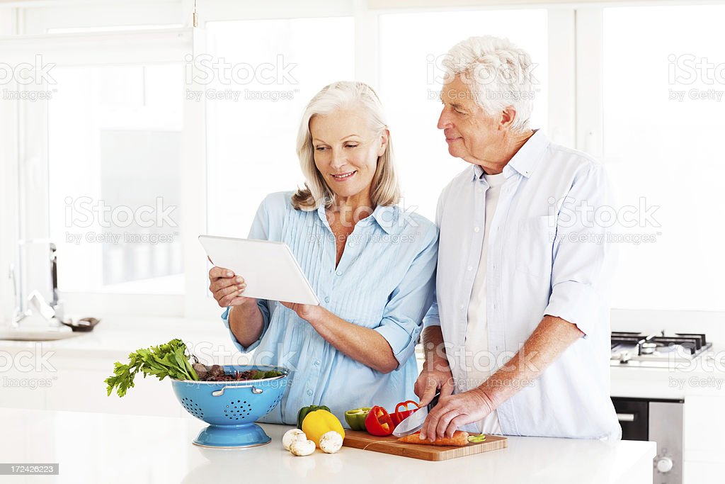 Couple With Digital Computer Cooking In Kitchen stock photo