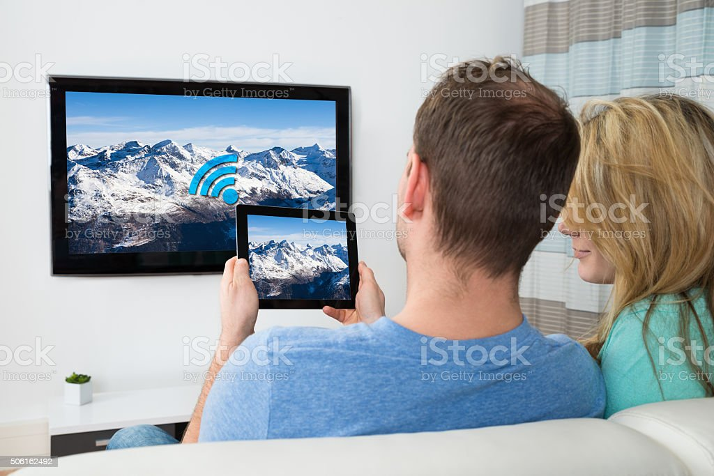 Couple With Digital Tablet And Television In Room stock photo