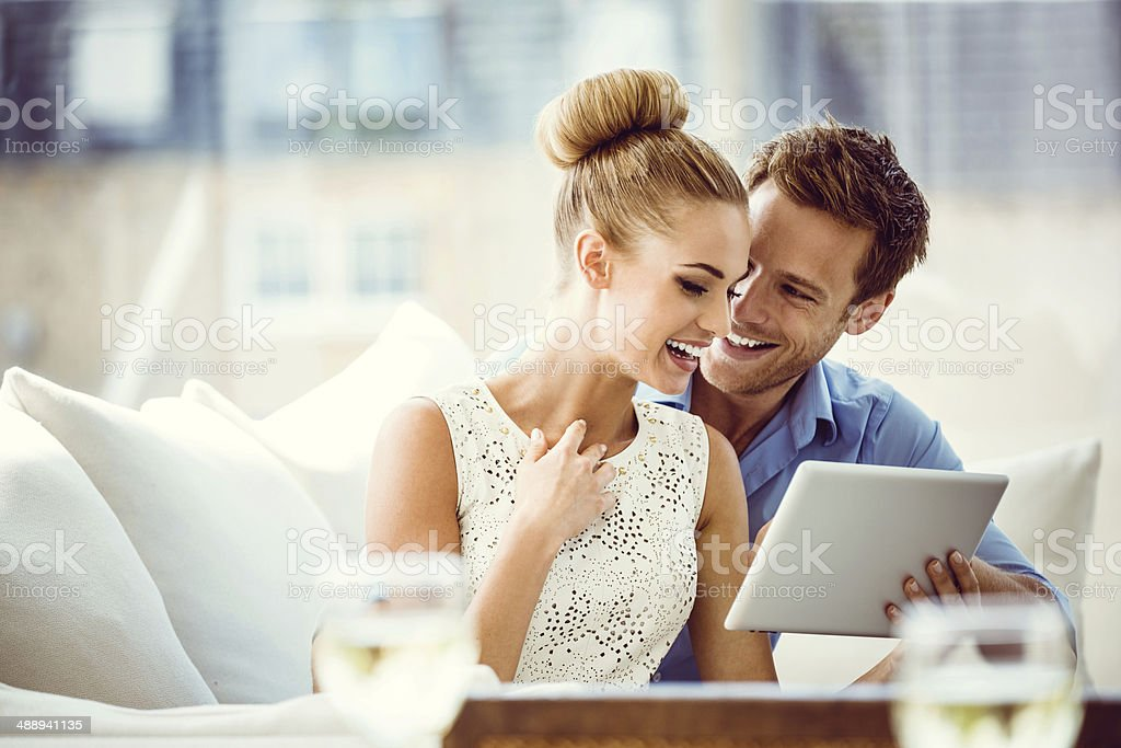Couple with digital tablet Portrait of happy couple sitting on sofa at home and using a digital tablet. 25-29 Years Stock Photo
