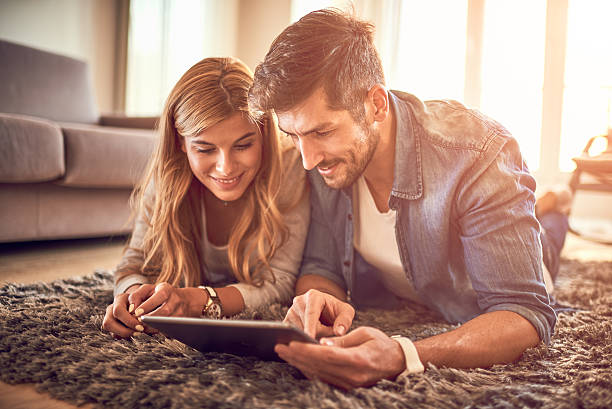 couple with digital tablet - mid adult couple stock pictures, royalty-free photos & images