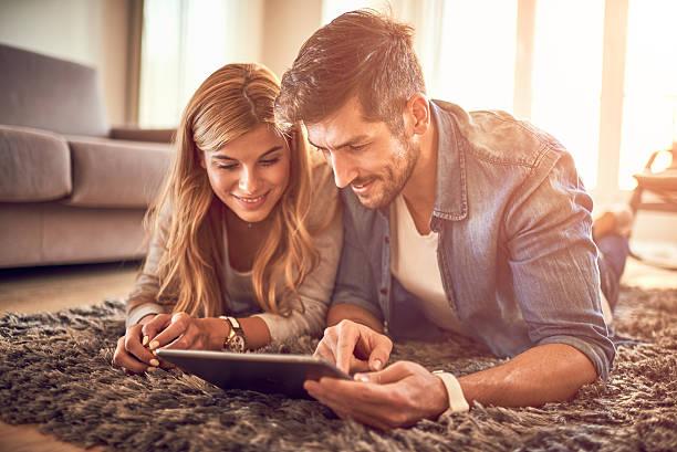 couple with digital tablet - mid volwassen koppel stockfoto's en -beelden