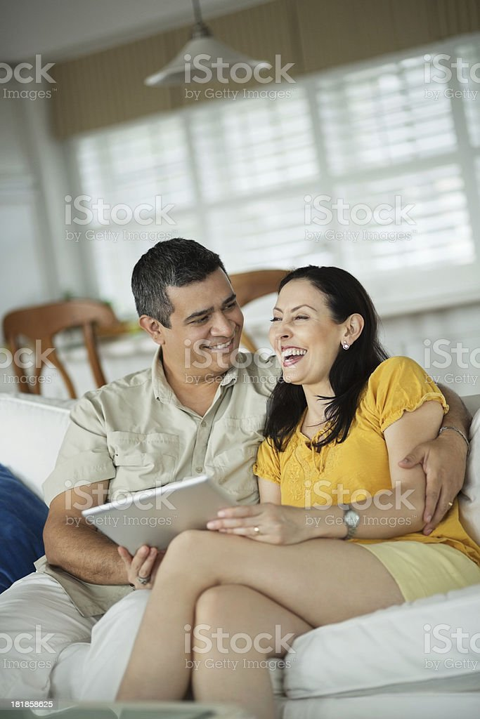 Couple With Digital Tablet Sitting On Sofa royalty-free stock photo