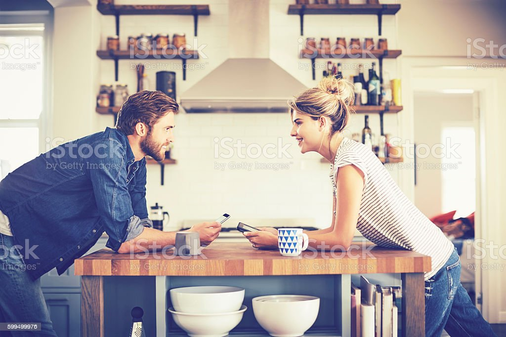 Couple with digital tablets leaning on kitchen island stock photo