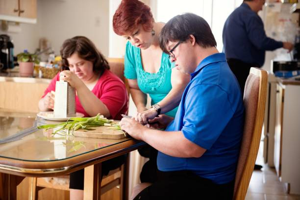 couple with down syndrome learning cooking cutting vegetables - manonallard stock photos and pictures