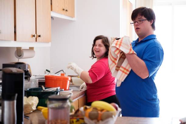 couple with down syndrome washing the dishes - manonallard stock photos and pictures