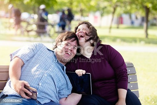 Couple in love of 26 years old Down Syndrome in a park in Montreal doing selfie with mobile phone. They are learning to live independently.  Color and horizontal photo was taken in Quebec Canada.