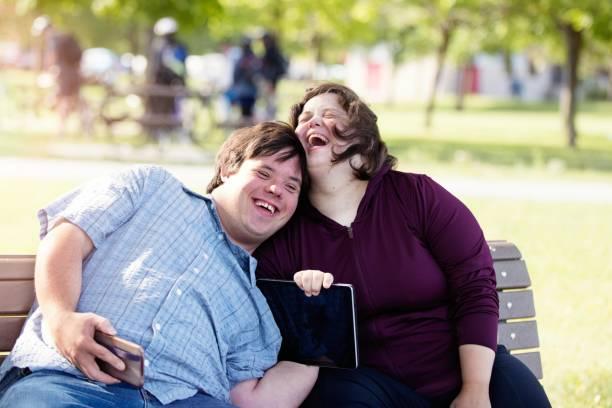 couple with down syndrome working doing selfie with mobile phone - aree esterne della scuola foto e immagini stock