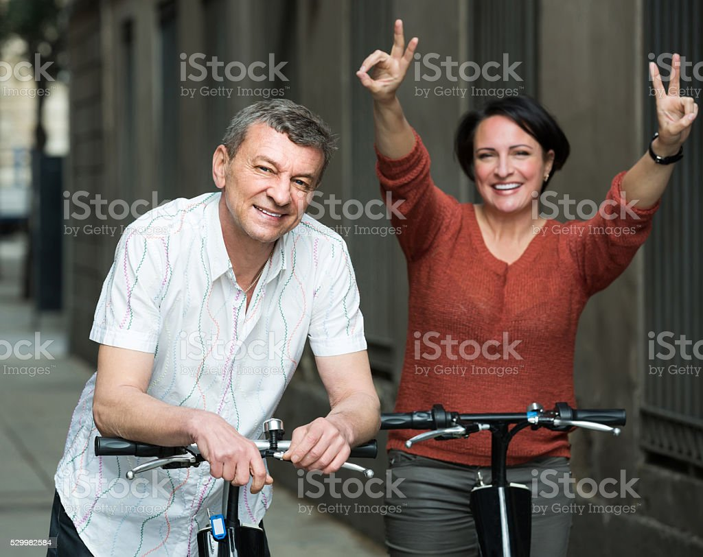 couple with electrkc bikes in vacation on city street stock photo