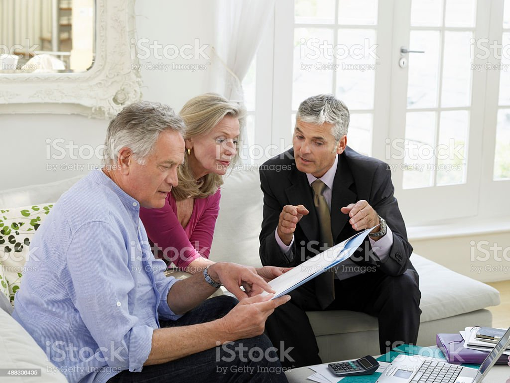 Couple With Financial Advisor At Sofa stock photo