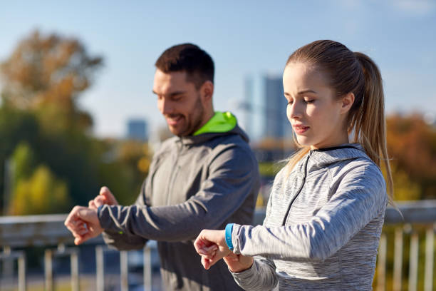 couple with fitness trackers training in city sport, people, technology and healthy lifestyle concept - couple with fitness trackers training in city woman taking pulse stock pictures, royalty-free photos & images