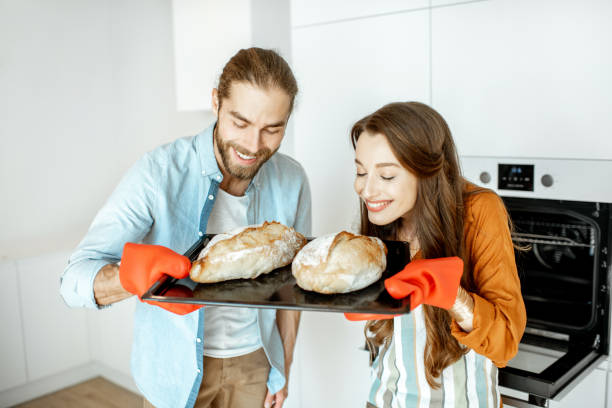 couple with fresh breads at the kitchen - baking bread at home imagens e fotografias de stock