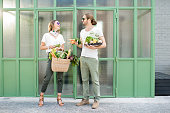 Young vegetarian couple standing together with bag and box full of fresh raw products from the local market outdoors on the green background