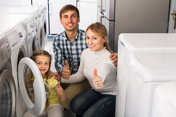 couple with girl selecting washing machine - happy person buy appliances stock photos and pictures