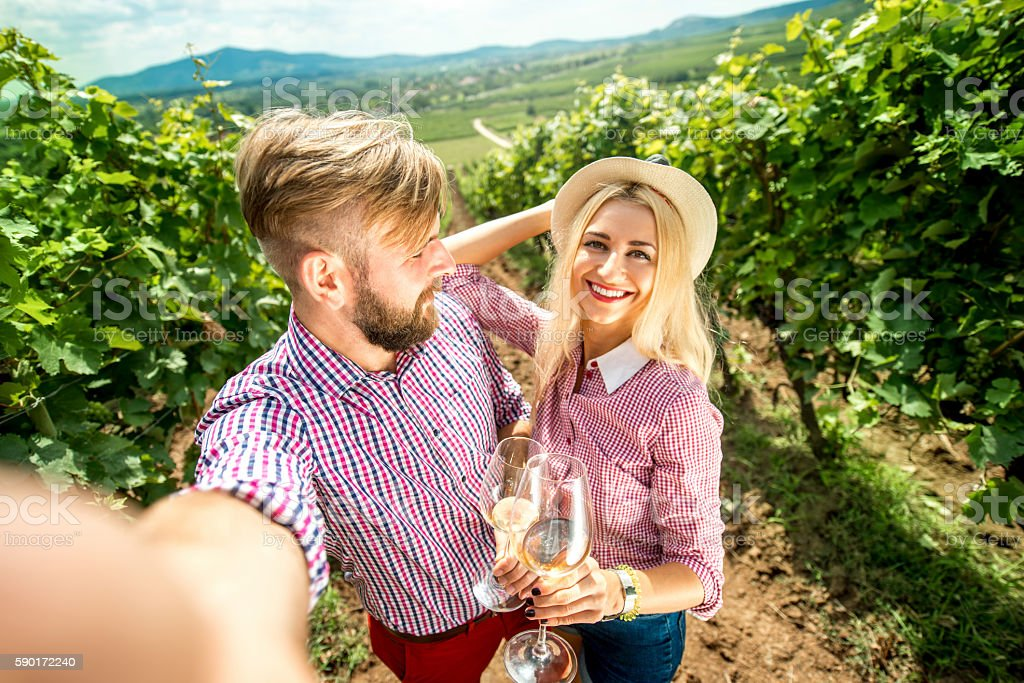 Couple with glasses of wine on the vineyard stock photo