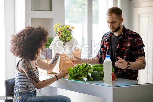Young woman holding bunch of flowers sitting by the kitchen bar counter with green vegetables, talking to flatmate