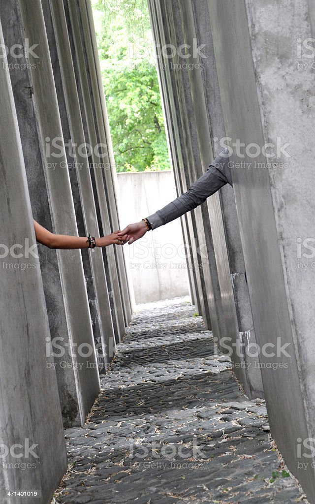 Couple with hands clasped into a labyrinthine gray pillars. stock photo