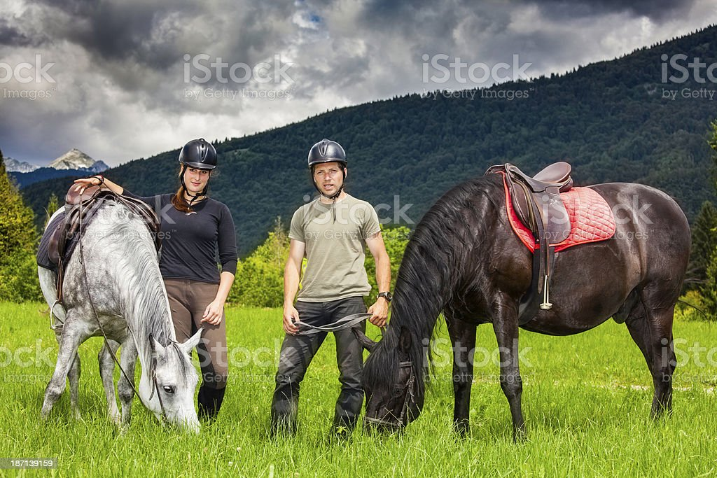 Couple With Horses Relaxing In Nature royalty-free stock photo