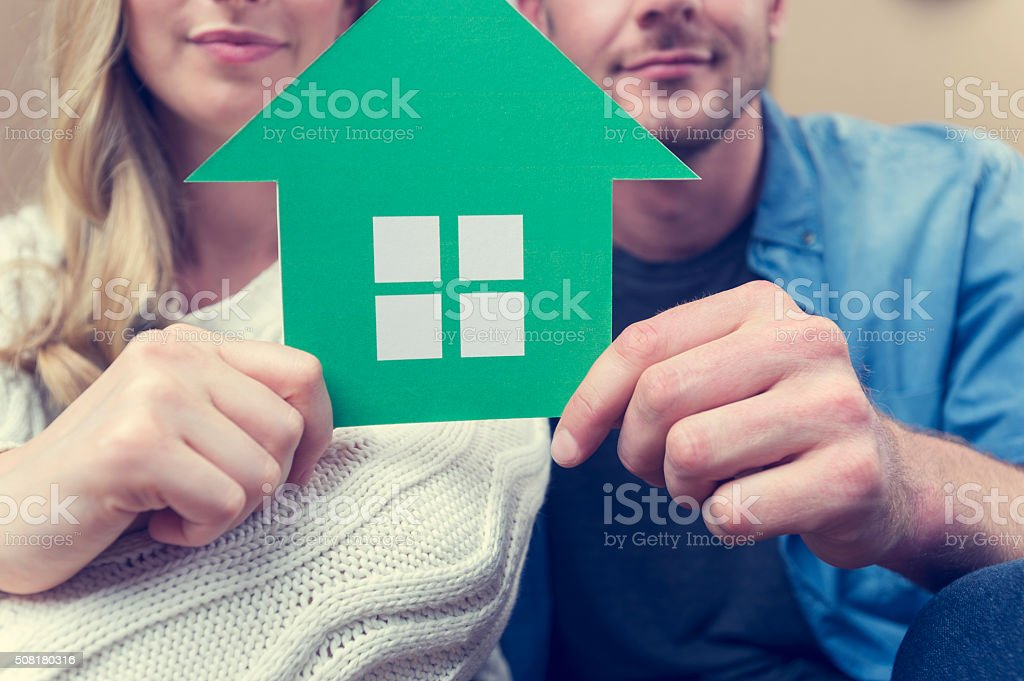 Couple with house symbol. Couple with house symbol. They are sitting down, smiling, both casually dressed and holding a green house symbol which could represent environmental conservation or home ownership. Adult Stock Photo