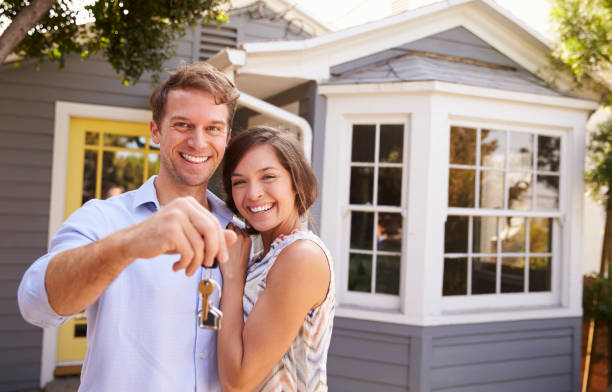 couple with keys standing outside new home - house hunting stock photos and pictures