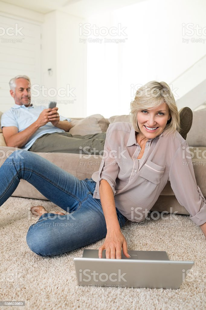 Couple with laptop and cellphone in living room at home stock photo