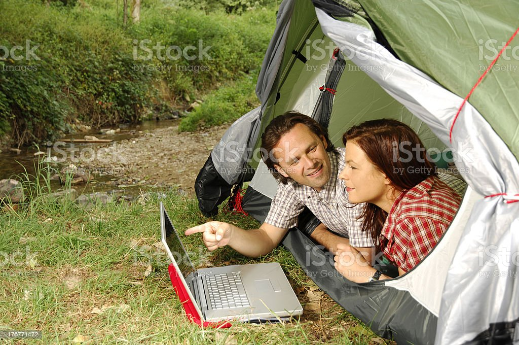 Couple with laptop - camping serie royalty-free stock photo