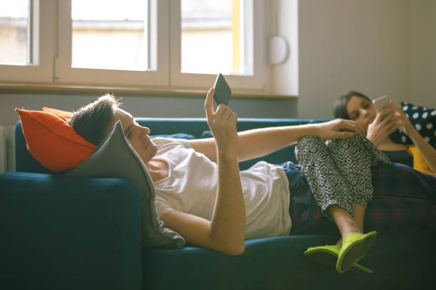 Couple with legs intertwined on the sofa using phones stock photo