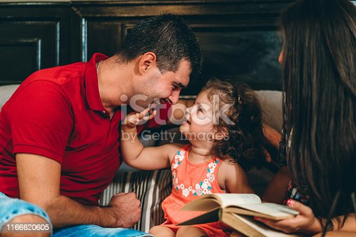 1070262182 istock photo Couple with little daughter reading book 1166620605