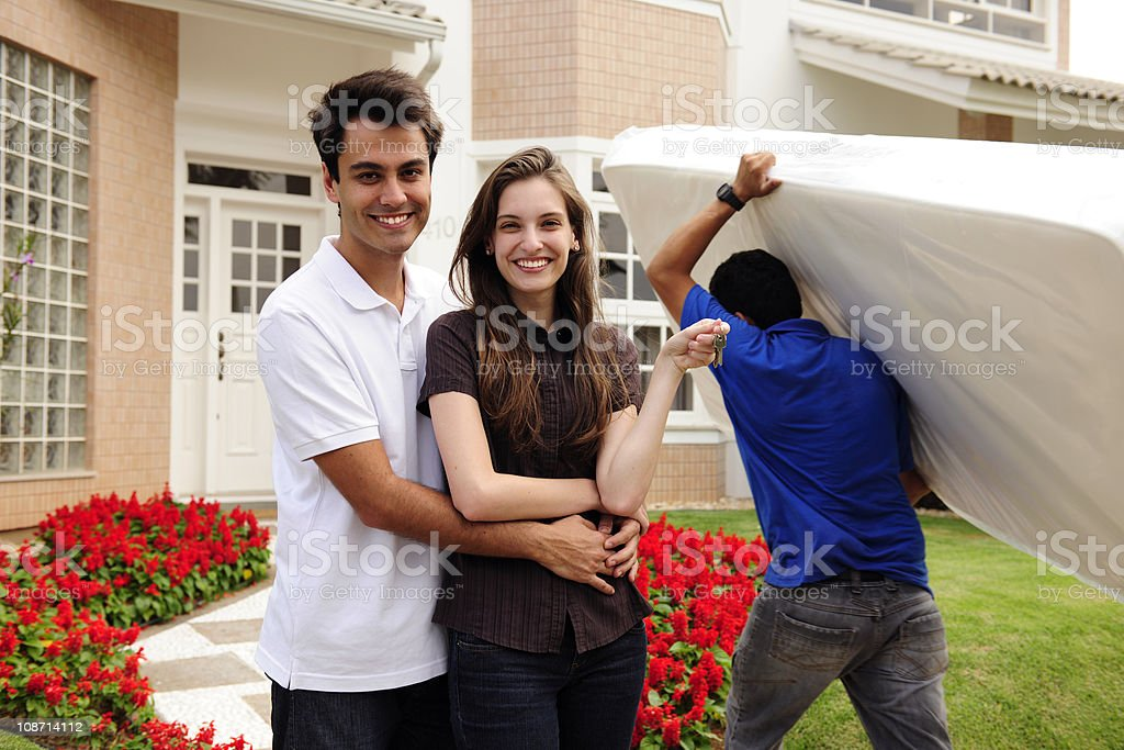 Couple with mover carrying a mattress stock photo