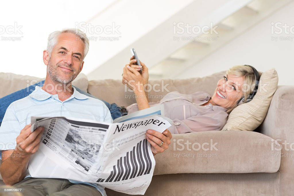 Couple with newspaper and cellphone in living room at home stock photo