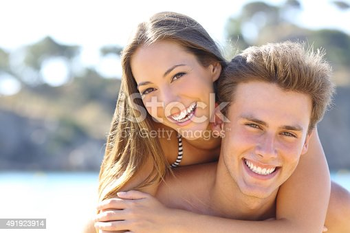 istock Couple with perfect smile posing on the beach 491923914