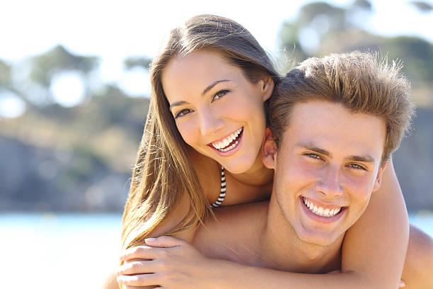 Pareja con sonrisa perfecta posando en la playa - foto de stock