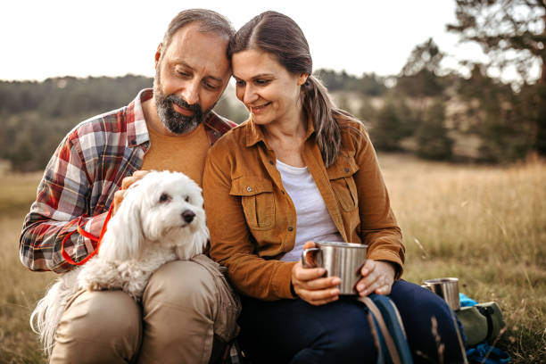 Couple with pet dog relaxing while hiking at forest stock photo