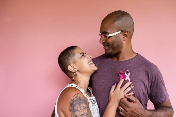 casal com fitas de outubro rosa na camisa - outubro rosa - fotografias e filmes do acervo