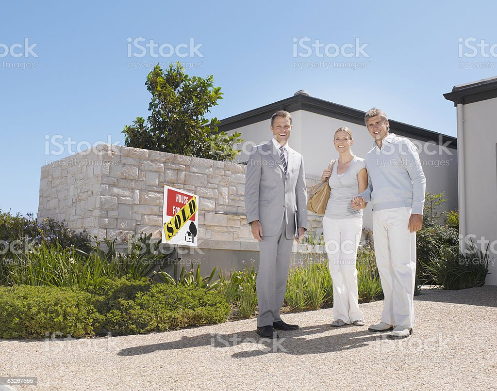 Couple with real estate agent at new home royalty-free stock photo